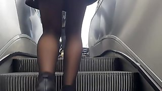 Sexy legs in shiny black pantyhose in metro